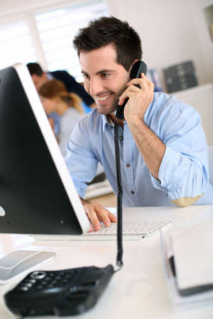 Smiling office worker talking on the phone