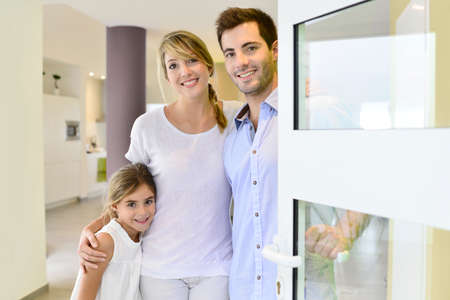 Family standing at front door to invite people in