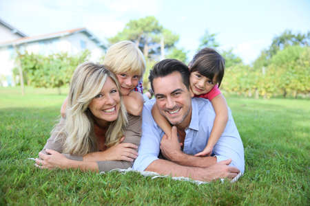 Family of four laying on grass in front of house