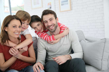 Cheerful family at home sitting in sofaの写真素材