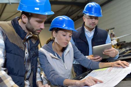Industrial engineers meeting in mechanical factory