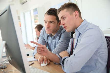 Teacher with student working on desktop