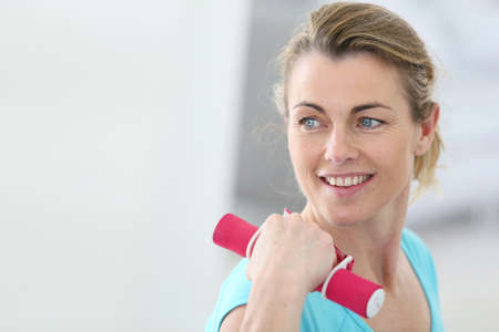 Portrait Of Mature Fitness Woman Lifting Dumbbells Royalty