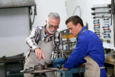 Young man in ironworks training with professional teacher