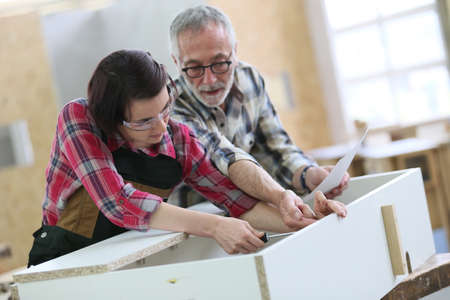 Young woman with senior craftsman in carpentry class
