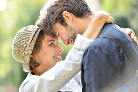 Romantic young couple embracing in park, sunlight