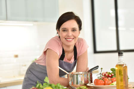 Portrait of beautiful woman cooking in home kitchen