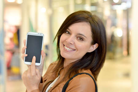 Woman in shopping mall showing smartphone