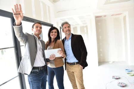 Photo pour Couple with realtor visiting house under construction - image libre de droit