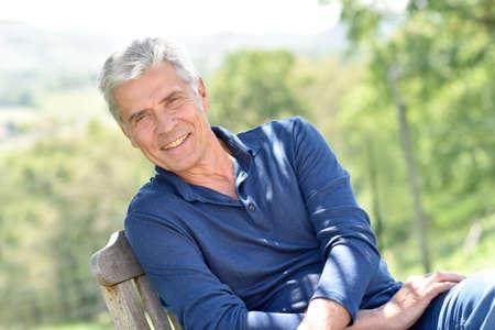 Photo pour Senior man relaxing in chair outside - image libre de droit