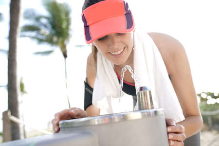 Fitness girl drinking from water fountain after exercising