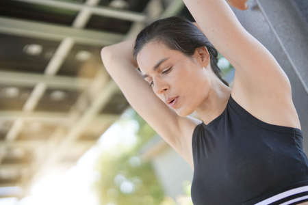 Brunette fitness girl stretching after exercising