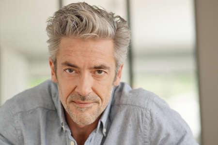 Photo for Portrait of handsome mature man looking at camera in contemporary home - Royalty Free Image