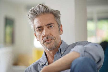 Photo pour Portrait of handsome mature man looking at camera in contemporary home - image libre de droit