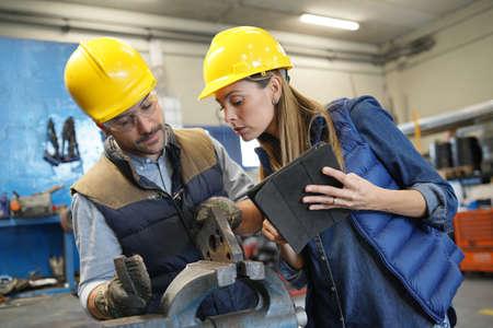 Photo pour Mechanical workshop manager giving instructions to employee - image libre de droit
