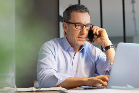 Foto de Business manager working in office talking on phone - Imagen libre de derechos