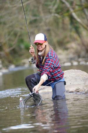 Photo pour woman catching rainbow trout fly in river - image libre de droit