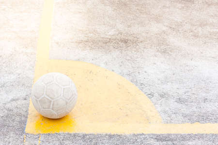 it's a ball of soccer or football place on yellow corner, ground is concrete
