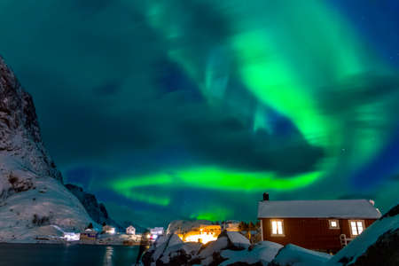 Winter Norway. Lofoten. Hamnoya town. Aurora Borealis above the roofs of houses
