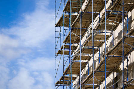 Photo pour Scaffolding near a new house under construction as the temporary support building structure during construction against the blue sky. - image libre de droit