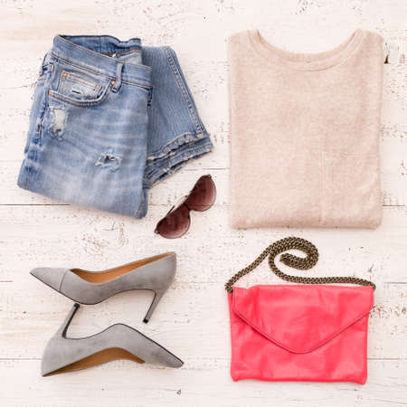 Photo pour Close-up of fashionable women's accessories: jacket, jeans, shoes, leather clutch and other accessories on a white wooden table - image libre de droit