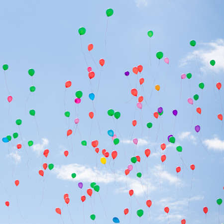 Photo pour Many colorful balloons fly in the blue sky. Bright festive event. Blue sky and clouds - image libre de droit