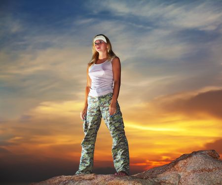 Military woman staying aon the mountain peak at sunrise time