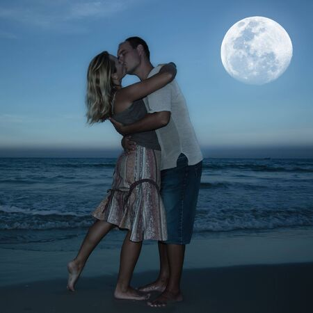 Young couple kissing at the beach under moonlightの写真素材