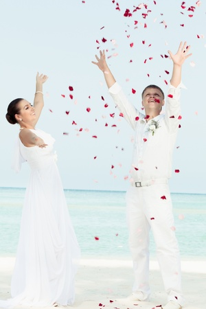 Bbride and groom throwing petals on the  beach
