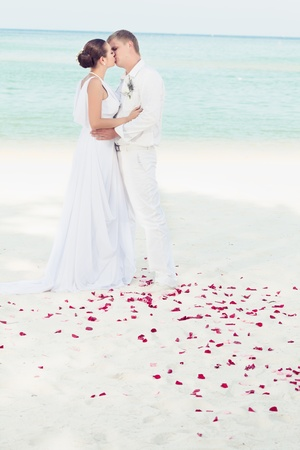 Bbride and groom kissing on the tropical beach