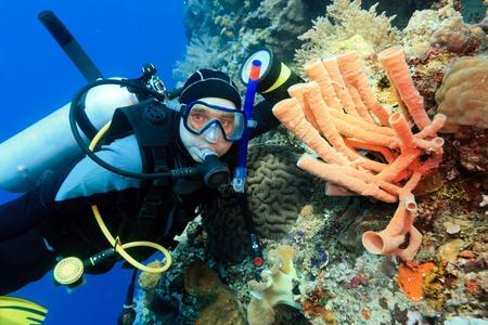 Scuba diver underwater close to coral reef