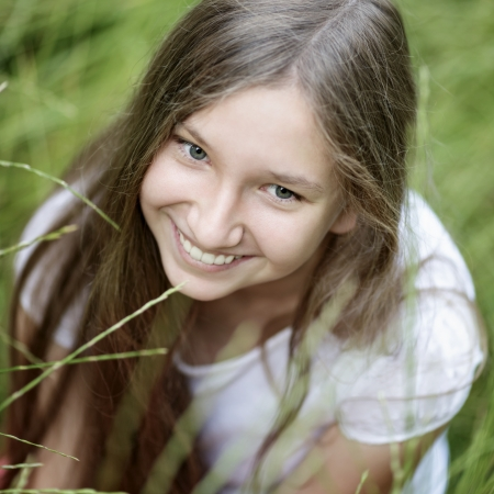 portrait of beautiful teen girl on the grass, upper point