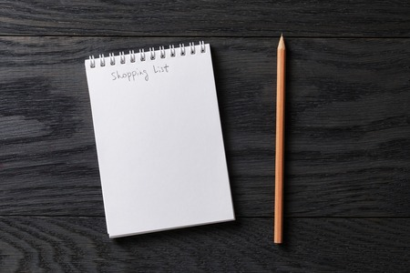 Foto de shopping list phrase in notepad on gray wood table, top view - Imagen libre de derechos