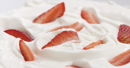 fresh sliced strawberries in cream background