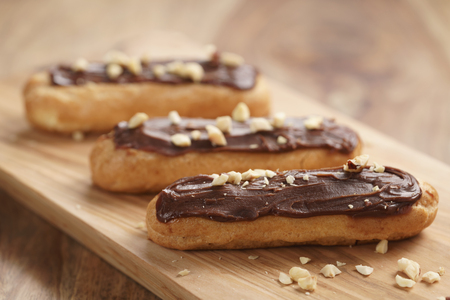 traditional french eclairs with chocolate and hazelnuts, shallow focus