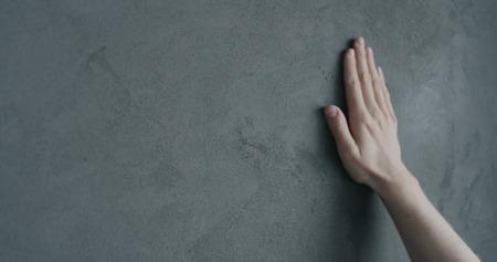 Photo pour man hand touches decorative concrete finish - image libre de droit