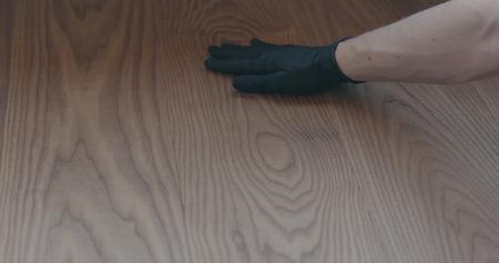 Photo pour closeup man hand touches ash wood floor - image libre de droit