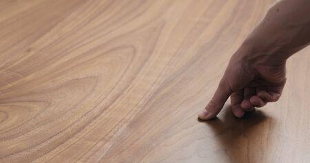 Photo pour man hand touches black walnut dining table surface - image libre de droit