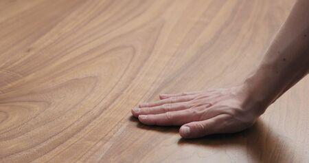 Photo pour man hand touches black walnut dining table surface, wide photo - image libre de droit