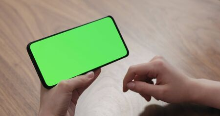 Photo pour Young woman sitting at a table and using a smartphone with horizontal green screen - image libre de droit