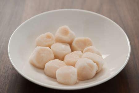 Photo pour frozen scallops in white bowl on walnut table for defrosting - image libre de droit