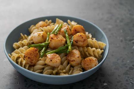 Photo pour Fusilli pasta with scallops and asparagus in blue bowl on concrete surface - image libre de droit