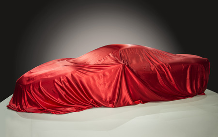 Sports car is covered with a red cloth