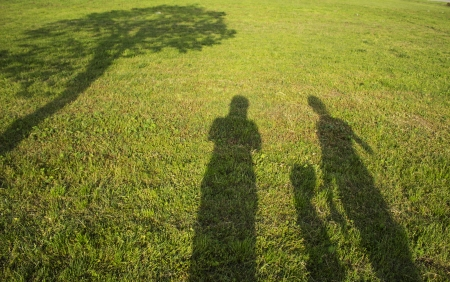 silhouette family with shadows in grass field