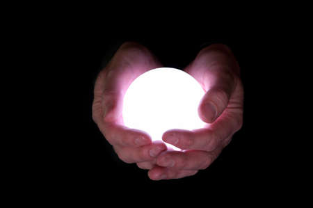 Business man holds glowing crystal ball against black background
