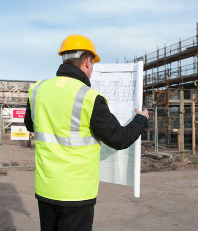 Architect or engineer at work on a building site. Checking plans against the construction work. Back to camera. Plans clearly visible.