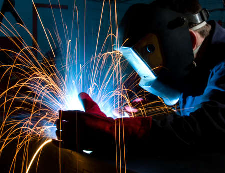 Arc welding in manufacturing plant. Close up with red glove.
