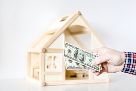 Foto de Hand giving one hundred us dollar banknotes. Wooden house model on background. Credit , debt or loan , real estate concept. - Imagen libre de derechos