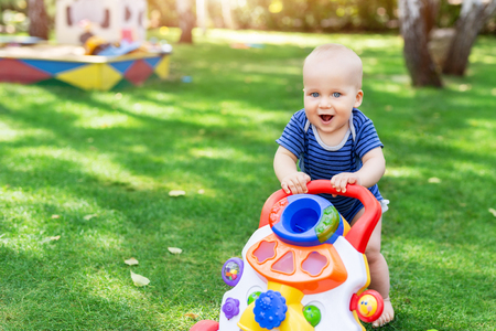 Foto de Cute little boy learning to walk with walker toy on green grass lawn at backyard. Baby laughing and having fun making first step at park on bright sunny day outdoors. Happy childhood and concept. - Imagen libre de derechos