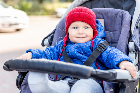 Foto de Cute little baby boy sitting in stroller and smiling during walk on cold autumn or winter day.Adorable kid wearing blue jacket and knitted red hat outdoors. Happy and healthy childhood concept. - Imagen libre de derechos
